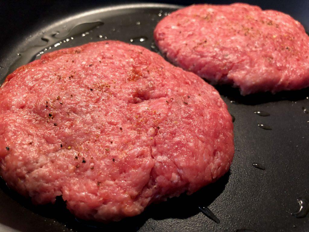 Burger-Patties aus Rindfleisch braten in der Pfanne